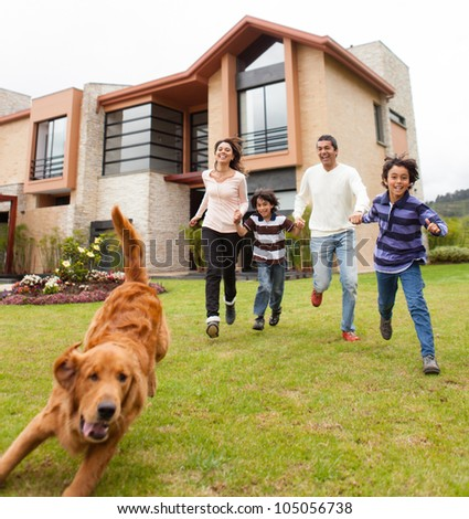 Family having fun running after the dog - stock photo