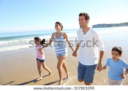 Family having fun running on the beach - stock photo