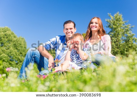 Family having fun sitting in the green grass