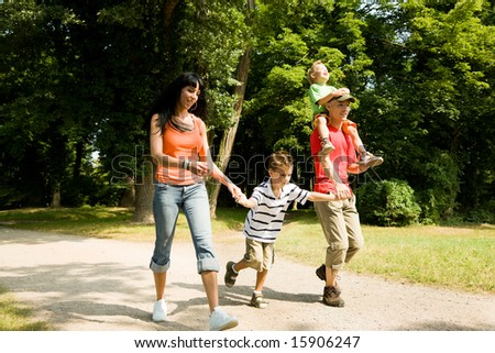 Family having fun, standing at the shore of a lake at a wonderful summer day (focus on the boy in front!) - stock photo