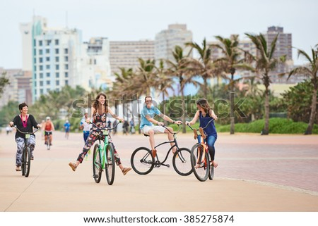 Family having fun together riding bicycles on urban pathway - stock photo