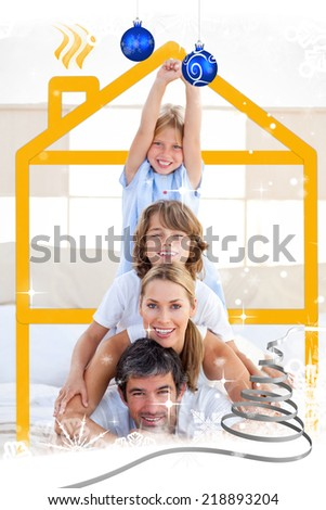 Family having fun with yellow drawing house against snow falling - stock photo