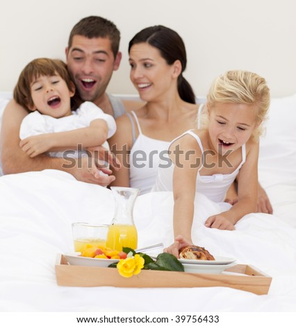 Family having nutritive breakfast  in bed in the morning - stock photo