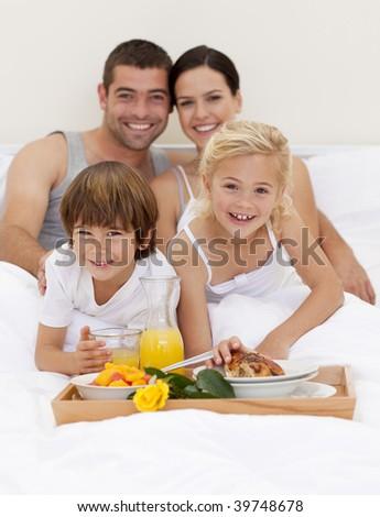 Family having nutritive breakfast in bedroom - stock photo