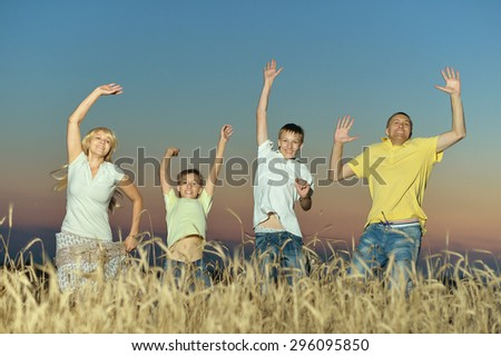 Family having rest in field at sunset