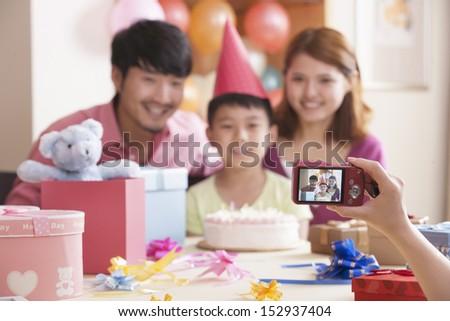 Family Having Their Picture Taken at Their Son's Birthday - stock photo