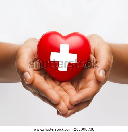 family health, charity and medicine concept - african american female hands holding red heart with cross sign - stock photo