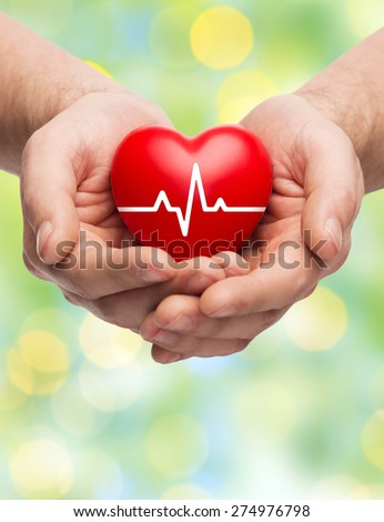 family health, charity and medicine concept - close up of hands holding red heart with cardiogram over green lights background - stock photo