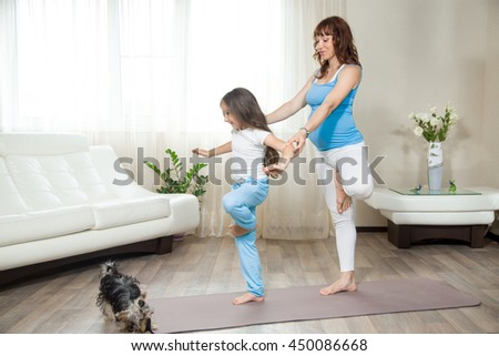 Family healthy lifestyle concept. Pregnancy Yoga and Fitness. Young happy pregnant yoga mom working out with little kid girl in living room interior. Pregnant mother teaching her child yoga at home - stock photo