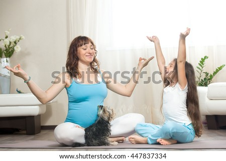 Family healthy lifestyle concept. Pregnancy Yoga and Fitness. Young pregnant mom meditating with dog and happy kid girl in living room. Child feeling joyful on meditation session with mother at home - stock photo