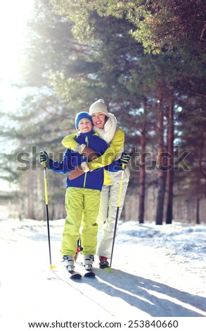 Family healthy lifestyle! Mother and son go skiing in the woods on a sunny winter day - stock photo