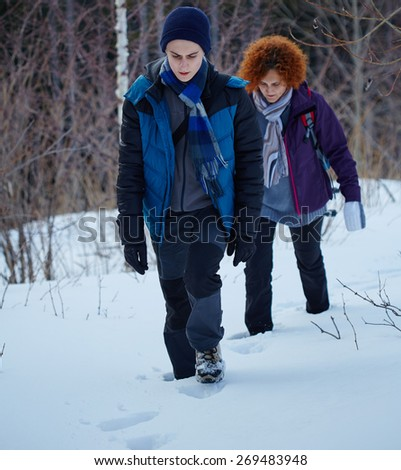 Family hikers walking through the snow near the forest - stock photo