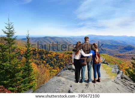 Family hiking in autumn mountains enjoying beautiful mountain view, North Carolina, USA. - stock photo