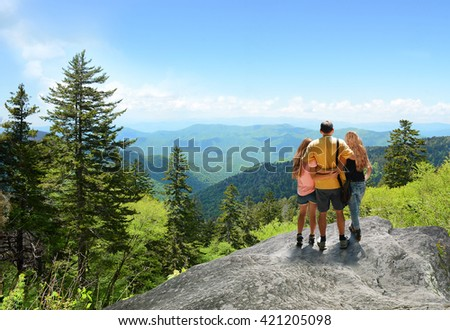 Family hiking on vacation, standing with arms around on top of the mountain, looking at beautiful summer mountains landscape. Blue sky in the background. Copy space. North Carolina, USA. - stock photo