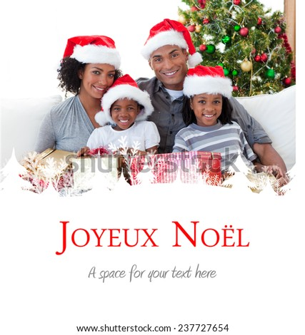 Family holding Christmas presents against joyeux noel - stock photo