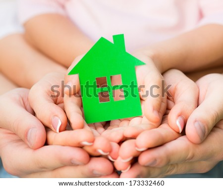 Family holding green paper house in hands. Real estate concept - stock photo