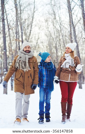 Family holding hands and walking through the forest in winter day - stock photo