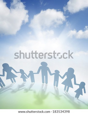 Family holding hands in front of bright sky - stock photo