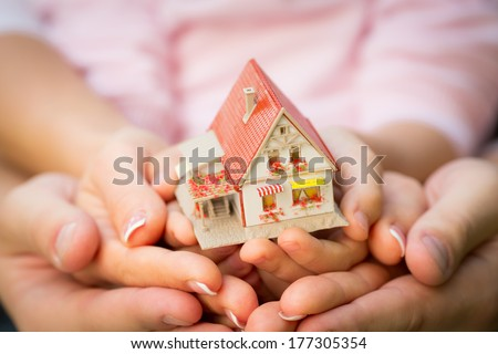 Family holding house in hands. Real estate concept - stock photo