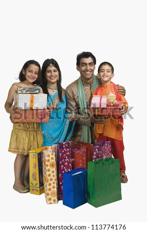 Family holding shopping bags and gifts for Diwali