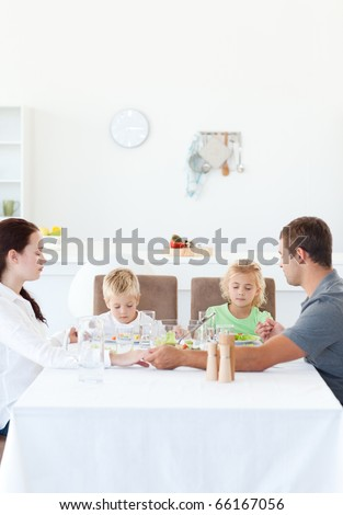 Family holding their hands while praying before eating a salad in the kitchen - stock photo