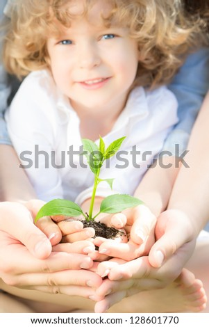 Family holding young green tree in spring. Ecology concept - stock photo