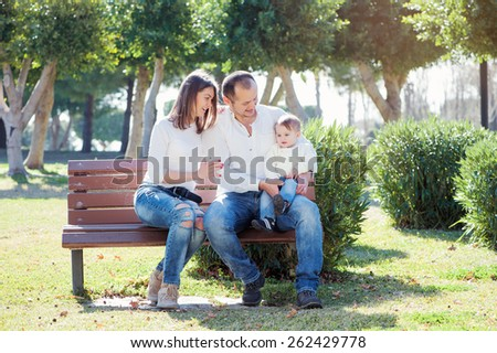 Family holiday. Happy young parents with little kid sitting on the bench in summer park. - stock photo