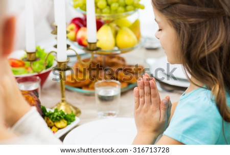 family, holiday, religion, thanksgiving, tradition and people concept - close up of girl praying at dinner at home - stock photo