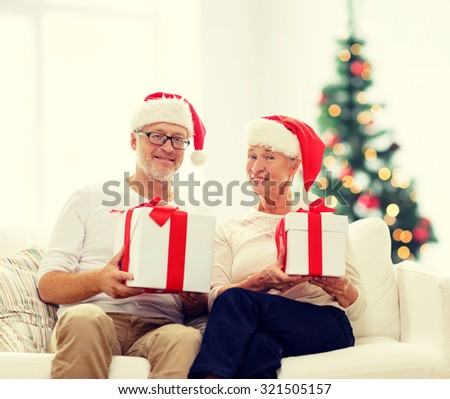 family, holidays, age and people concept - happy senior couple in santa helper hats with gift boxes over living room and christmas tree background