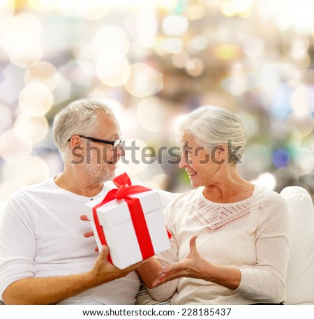 family, holidays, christmas, age and people concept - happy senior couple with gift box over lights background