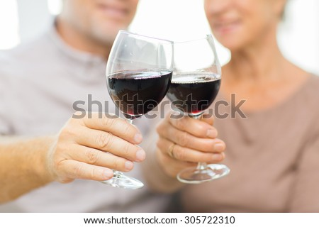 family, holidays, drinks, age and people concept - close up of happy senior couple clinking glasses with red wine at home - stock photo