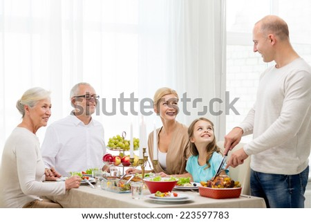 family, holidays, generation and people concept - smiling family having dinner at home