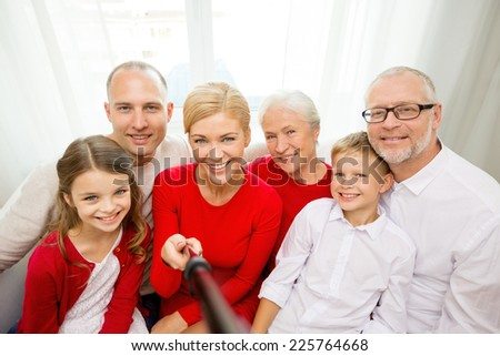 family, holidays, generation, christmas and people concept - smiling family with camera and selfie stick taking picture at home - stock photo