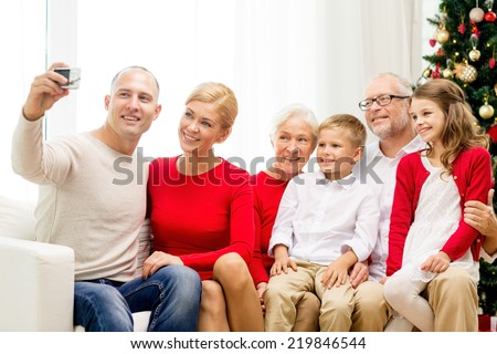 family, holidays, generation, christmas and people concept - smiling family with camera making selfie and sitting on couch at home - stock photo