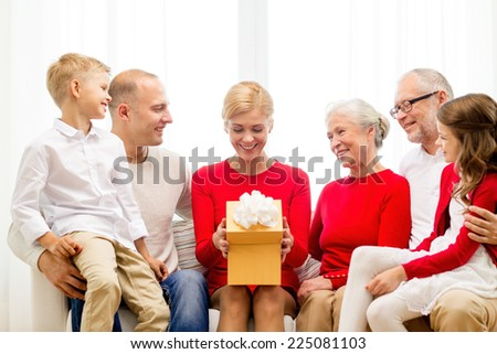 family, holidays, generation, christmas and people concept - smiling family with gift box sitting on couch at home