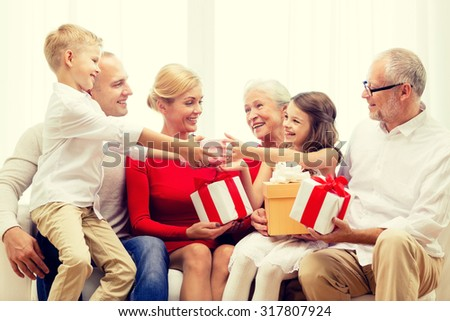 family, holidays, generation, christmas and people concept - smiling family with gift boxes sitting on couch at home - stock photo