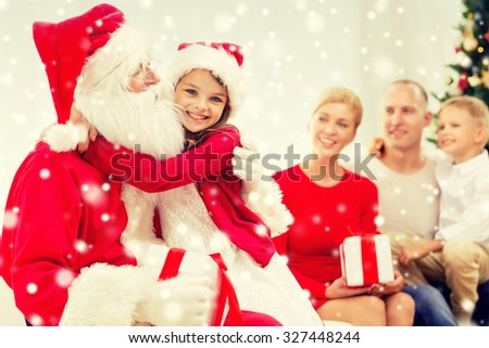 family, holidays, generation, christmas and people concept - smiling family with santa claus and gift boxes at home - stock photo