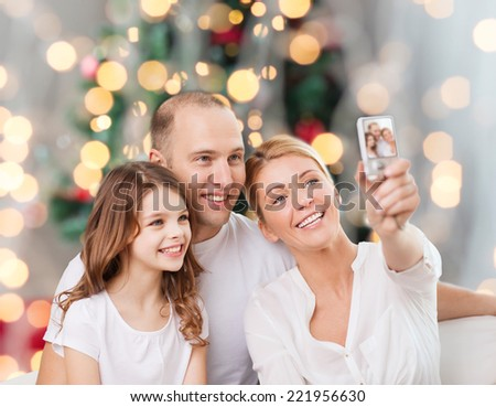 family, holidays, technology and people concept - smiling mother, father and little girl making selfie with camera over christmas tree lights background - stock photo