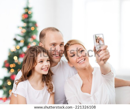 family,  holidays, technology and people - smiling mother, father and little girl making selfie with camera over living room and christmas tree background - stock photo