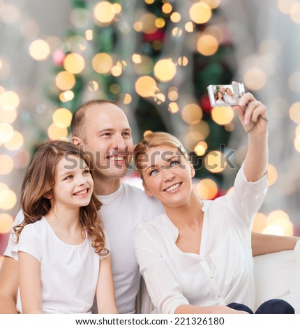 family, holidays, technology and people - smiling mother, father and little girl making selfie with camera over christmas tree lights background - stock photo