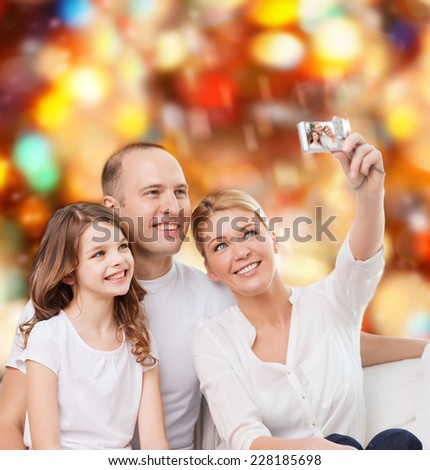 family, holidays, technology and people - smiling mother, father and little girl making selfie with camera over red lights background - stock photo