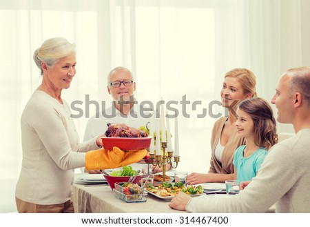 family, holidays, thanksgiving, generation and people concept - smiling family having dinner at home - stock photo