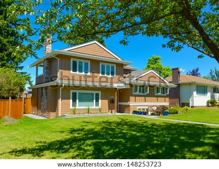 Family house in suburban area of Vancouver, Canada. North American house on blue sky background on a sunny day