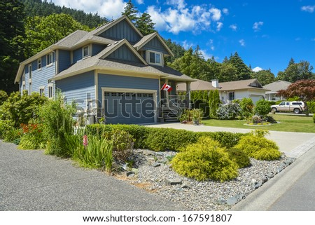 Family house with landscaping on the front and blue sky background. House with concrete driveway and wide double garage.