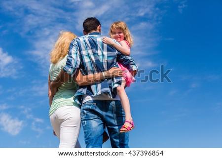 Family, hugging, backs to camera, slight low angle shot - stock photo