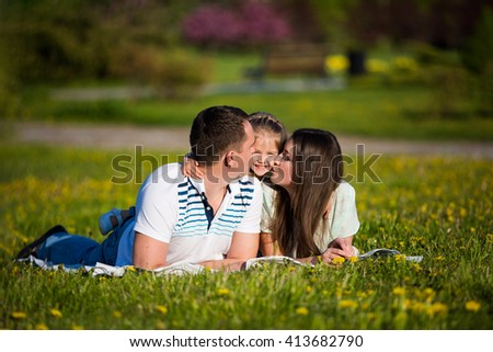 Family hugging together on the green grass flowery lawn: mother, father and little girl