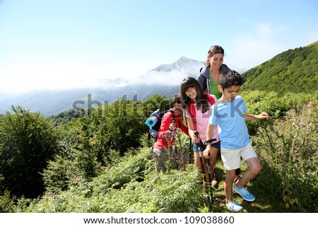 Family in a hikking day climbing up the hill
