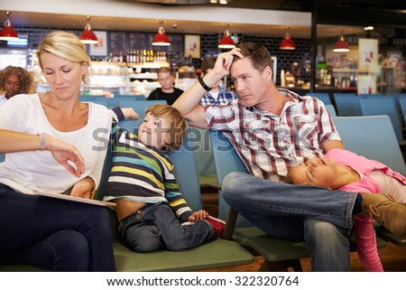 Family In Airport Departure Lounge Wait For Delayed Flight - stock photo
