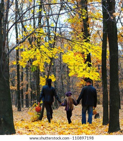 Family in autumn forest. Walk for hands of a happy family from three persons