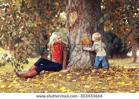 Family in autumn park! Happy mother and child having fun together  - stock photo